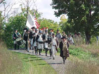 Re-enactors led by Dave Bernier, of Southampton, MA portraying American General Horatio Gates, bring Colors forward.