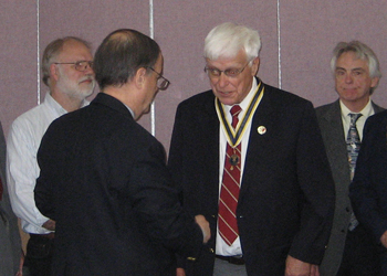 Past President Richard W. Sage congratulates dual chapter member President Duane Booth after presenting him with the Society's State President Medallion