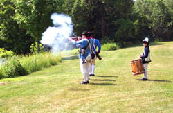 Members of the Saratoga National Historical Park staff and volunteers in Colonial soldier's uniform perform a musket firing demonstration.