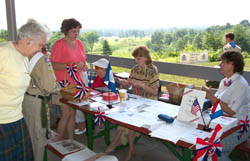 Members of the Saratoga Chapter, Daughters of the American Revolution (DAR), Bemis Heights Society and the Children of the American Revolution (CAR) distribute brochures and sell raffle tickets.