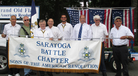 The author, Dennis Booth (green shirt), is recruited to carry the chapter's standard. (L-R) R. Harry Booth, Dennis Booth, SBC President Tom Dunne, WB President John H. Sheaff, SBC Past President Primitivo Africa, VT Society President Douglass 'Tim' Mabee, SBC Past President Duane Booth, Patrick Festa