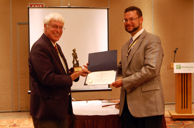 President Africa presents Past President Duane Booth with the Duane Booth Minuteman award.  A photo of the certificate and the statue seen on the front page of the website in the 'Photo Highlight' area (lower right)- Photo: Joyce Armstrong